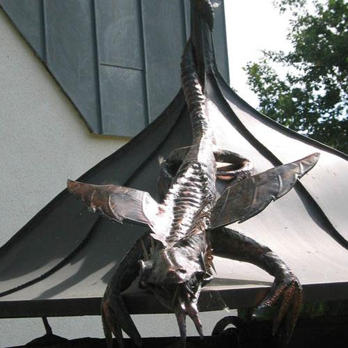 Brunnendachabdeckung am Firmengebäude, handgefertigtes Fabeltier erstellt von Dachdeckerei C. Voegeli Udo Heyl